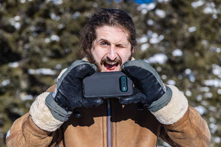 Dramatically ironic portrait of a young man in a winter coat taking a picture with his mobile phone while making an exaggerated funny face. Standard-Bild