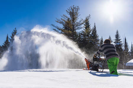 Wide angle rear view of a man creating a huge glistening snow blizzard while removing fresh knee deep snow with a mechanical snowplough. Sunny day. Standard-Bild