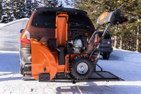 A bright orange mechanical snowplough is parked in front of a car in a driveway, ready to be used to remove snow in a canadian country house.