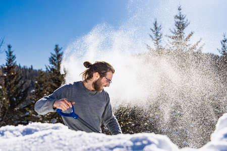 Side view of a young man energetically throwing a heap of fresh snow, creating a blizzard, using a blue hand shovel in a sunny canadian winter day.