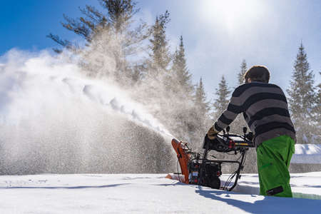 Rear view of a young man pushing an orange mechanical snowplough in the knee deep fresh snow, with a big jet of snow exiting the machine.