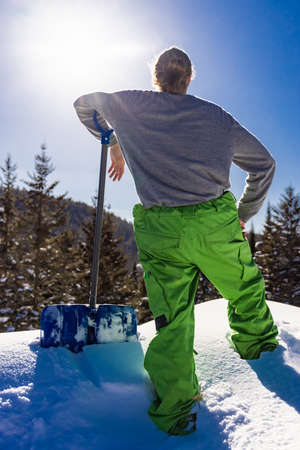Close up, rear view of a young man leaning on the handle of a blue snow shovel while taking a break during a snow removal job in a country house. Standard-Bild