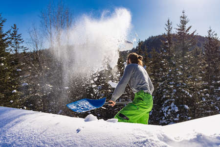 View from behind of a young man energetically removing fresh snow from a roof with a blue hand shovel, throwing heaps of fresh snow over the edge.