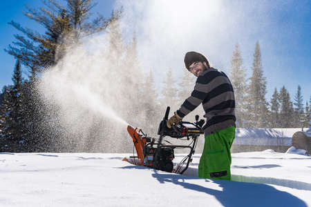 Smiling young man maneuvering an orange mechanical snowplough in the knee deep fresh snow, with a big jet of snow exiting the machine like a snowstorm