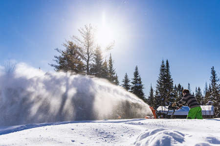 Wide angle side view of a man creating a huge glistening snow blizzard while removing fresh snow with a mechanical snowplough in a sunny winter day.