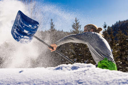 Side view of a young man energetically throwing a heap of fresh snow to the side using a blue hand shovel in a sunny canadian winter day. Standard-Bild