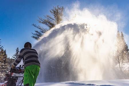 Close up shot of a yong man digging a path in the snow with an orange mechanical snowplough and rising to the sky a huge jet of glistening snow.