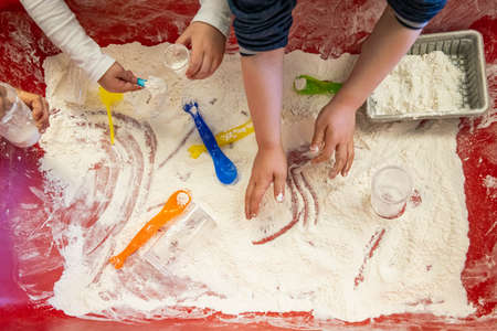 Close up shot from above of two pairs of kid hands playing with a sandy material on the colored table of the indoor play area. Experimenting. Standard-Bild
