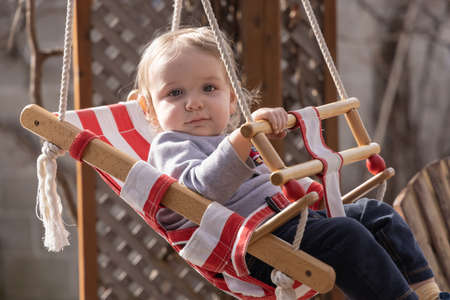Close up shot of a cute little blond canadian boy relaxing in a wooden backyard swing with red and white fabric, ooking happily at camera. Standard-Bild