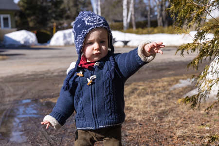 Close up shot of a cute canadian baby boy with blue winter jersey and winter wool playing outdoor in a sunny day, in the melting late winter snow.