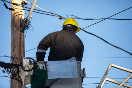 A zoomed in snapshot taken from the backside, a man sitting on the chair, in the protected uniform, fixing some fault in the electricity pole