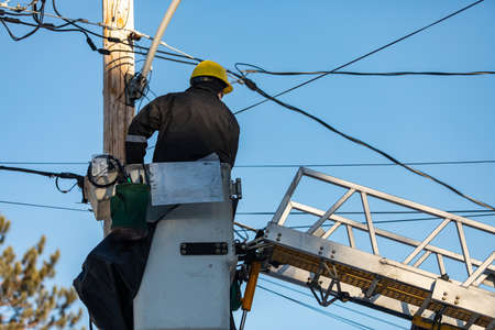 A back view of an electrical engineer sitting on a platform attached with the ladder, working with cables and fixing some technical fault Standard-Bild