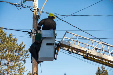 An upright shot of a technician from electric supply company, wearing a safety kit, sitting on the top of a ladder attached with the electricity pole Standard-Bild