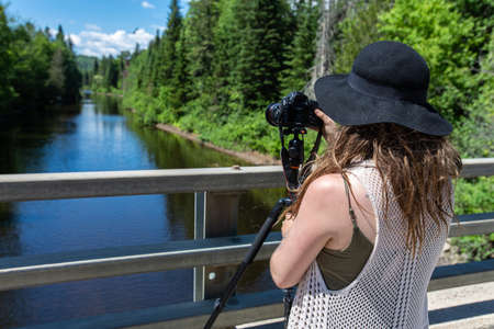 A backside of a woman, wearing a black hat, with a professional camera on the tripod, trying to capture an amazing view of the lake covered with trees Standard-Bild