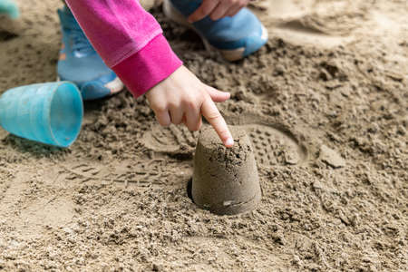 A picture of a child hands, wearing pink jacket and blue joggers, playing on sand while pointing on a sand model, made with a blue mold.