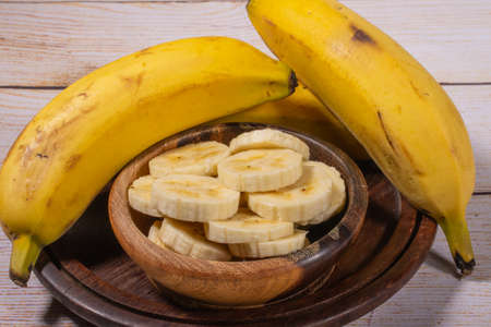 Banana cut into slices in a wooden bowl in the highlight and in the background bananas in a wicker basket on a light wooden background.