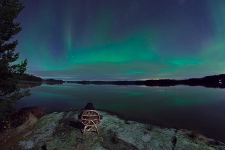Sitting in the chair next to the water at night. Bright green aurora borealis in the sky.