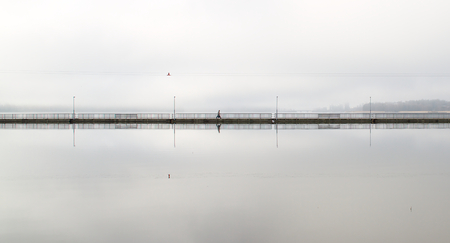 Lonely walker on a long empty bridge early in the morning. Grey and foggy weather in the city. Stok Fotoğraf