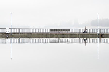 Man going to work on a long bridge, early morning in the city. Morning fog still covering the sea and blurring the silhouette of the city on the background. Clear reflection from steady water surface. Stok Fotoğraf