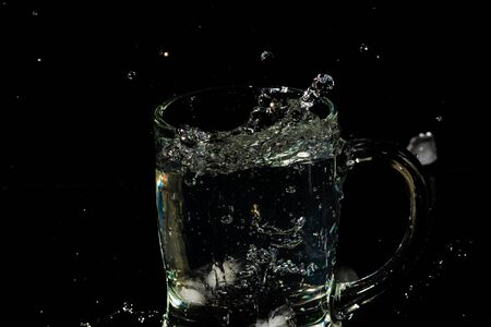 glass mug filled with water and ice with splash effect and black background