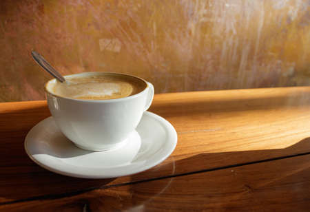 cup of coffee on a wooden table and late afternoon sunlight illuminating Фото со стока