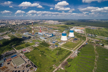 closed community: aerial view of power plant. It is on the outskirts of the city. From its two large white - blue pipe is steam. It is surrounded by greenery Stock Photo