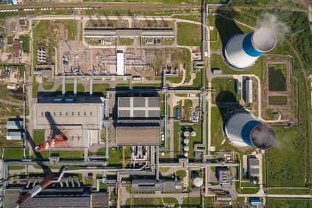 tall chimney: aerial view of power plant. It is on the outskirts of the city. From its two large white - blue pipe is steam. It is surrounded by greenery Stock Photo