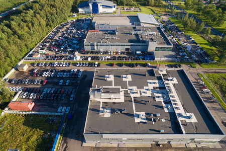 automobile dealer: Aerial view of the automobile dealer center. It consists of several buildings with bright colors, surrounding is a large number of new cars. Russia, 2016