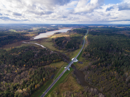 Beautiful aerial view of road bridge over the river surrounded by forest. The Republic of Karelia. On the bridge one lane in each direction. Behind him one can see meadows, lakes and fields. On the sky clouds float. Russia, 2016