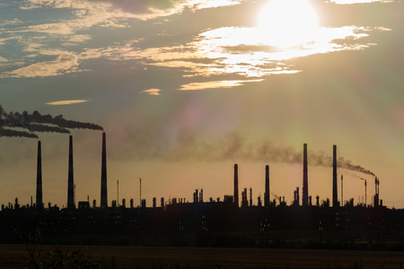 The silhouette of a huge gas and oil processing plant with burning torches, pipes and distillation of the complex