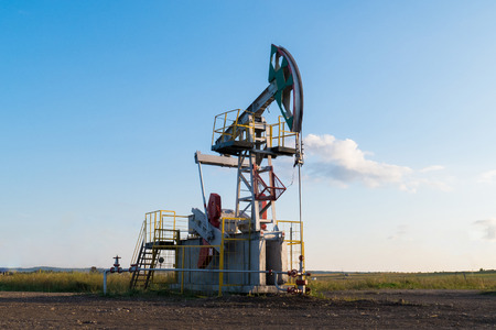 working oil pump on the ground among the green fields Stock Photo