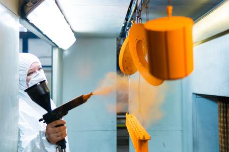 Malowanie proszkowe części metalowych. Kobieta w kombinezonie ochronnym rozpyla farbę proszkową z pistoletu na produkty metalowe