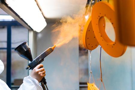 Recubrimiento en polvo de piezas metálicas. Una mujer en un traje protector rocía pintura en polvo de una pistola sobre productos metálicos Foto de archivo