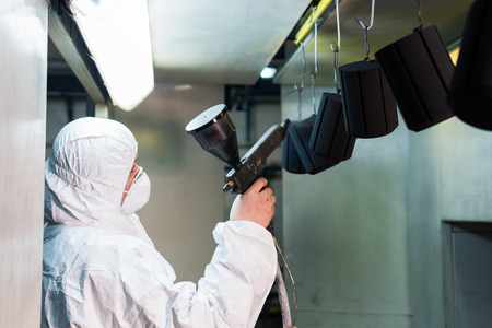 Powder coating of metal parts. A man in a protective suit sprays powder paint from a gun on metal products Stockfoto