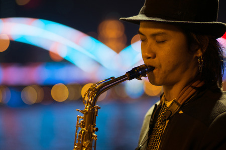 Guangzhou, China - MARCH 15, 2016: man playing saxophone on the street in the evening