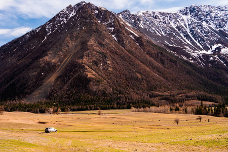 incredible scenery of the mountain valleys of the Altai mountains with cliffs and snow-capped peaks at the foot of which is a car of tourists