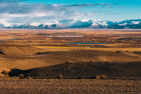 incredible landscape of the steppe area with lakes and trees smoothly turning into mountains with snow-capped peaks. Mountains Of Altai
