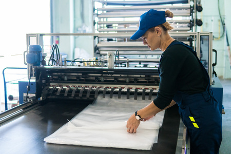 woman worker in the production of plastic packaging folds finished products