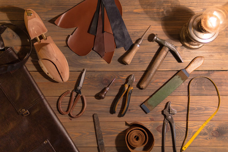 tools for making shoes lie on a wooden table. Set of items symbolizing manual labor, small business