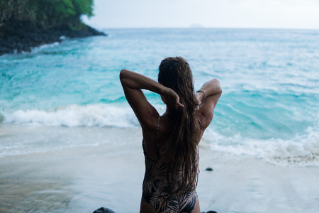 beautiful long-haired tanned girl of European appearance posing for the camera on the background of the ocean beach, stones and trees. Indonesia, Bali Stock Photo