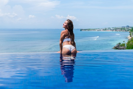 sexy girl. beautiful woman. model lady bikini underwear big ass butt booty sit edge of water swim pool on the roof of luxury resort hotel nice sea scenery long shot