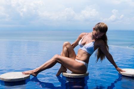 meisje. mooie vrouw. model dame bikini ondergoed zitten rand van water zwembad op het dak van luxe resort hotel mooi zee landschap afstandsschot Stockfoto