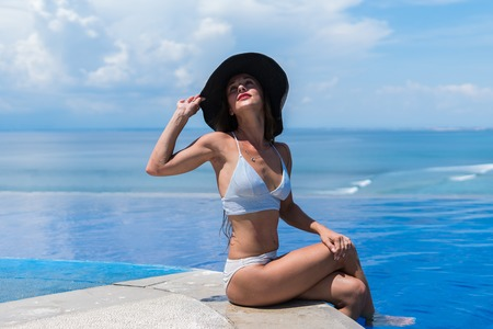 Attractive woman in bikini and with grey hat is relaxing in an infinity pool Stok Fotoğraf