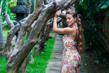 Beautiful young woman is leaning against a tree in the rain forest wearing sexy dress