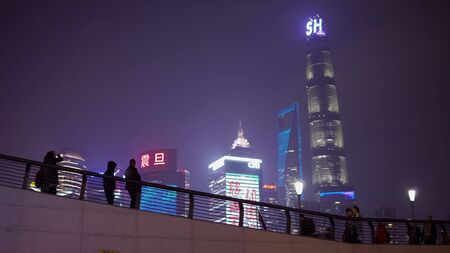 Shanghai, China - January 15, 2018: People walk along the embankment of Vaitan at the night. The Bund or Waitan is a waterfront area in central Shanghai