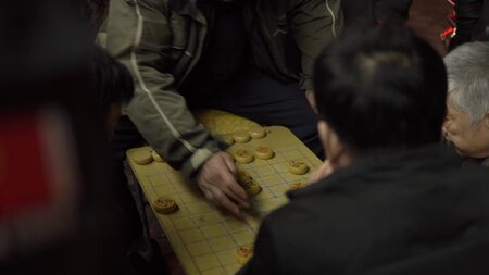 Shanghai, China - January 15, 2018: Group of few people plaing xiangqi. Xiangqi, also called Chinese chess, is one of the most popular board games in China 新聞圖片