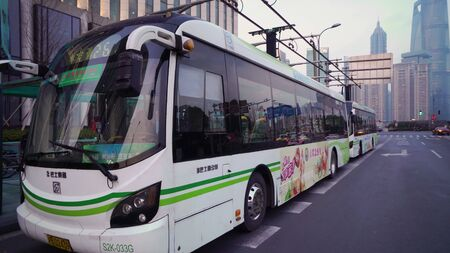 Shanghai, China - January 15, 2018: Electric powered hybrid bus charging on street near bus stop