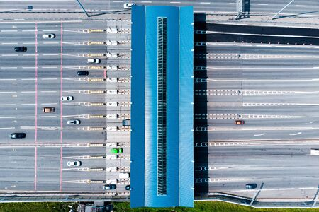 Toll roads on the broad highway. Through the point passes a large number of trucks and cars. Top down view from quadcopter