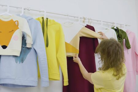 Female fashion designer works on new womenswear collection for clients workshop studio, dressmaker, tailor or needlewoman standing near clothing rack with fashionable stylish handmade clothes