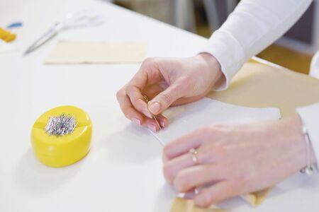 Freiberuflerin, Modedesignerin oder Schneiderin, die in der Werkstatt an einem Design oder Entwurf mit bunten Stoffen arbeitet. Nahansicht